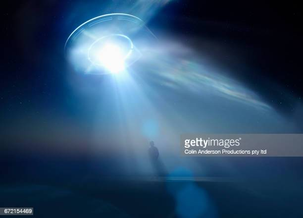 Caucasian man standing in beam of light from UFO