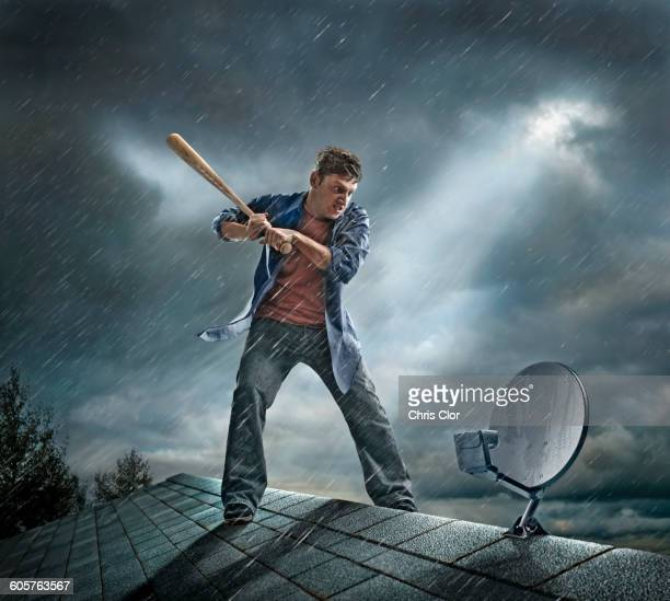 caucasian man swinging baseball bat at satellite dish on roof - one young man only stock illustrations