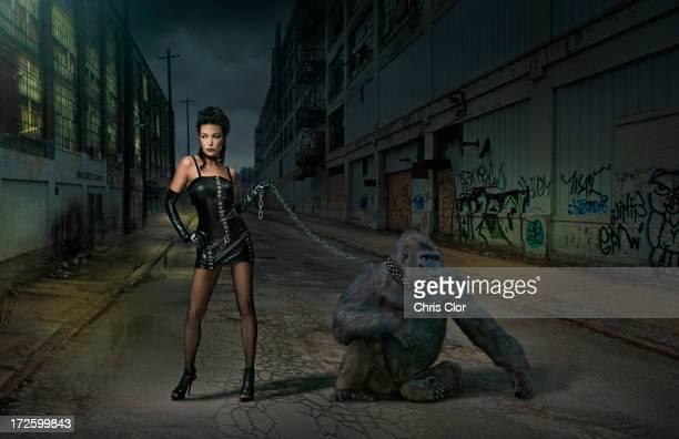 Caucasian woman with gorilla on chain on city street