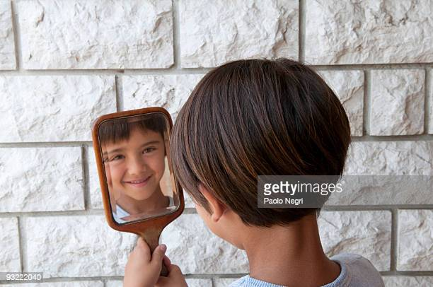 child smiles while watching himself in the mirror