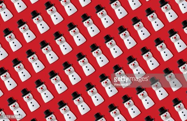 christmas snowmen pattern against red background - human representation stock illustrations