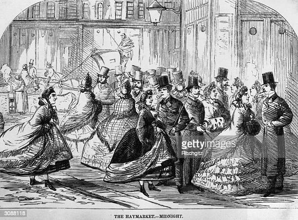 Prostitutes making their advances to a group of men at midnight in London's Haymarket.