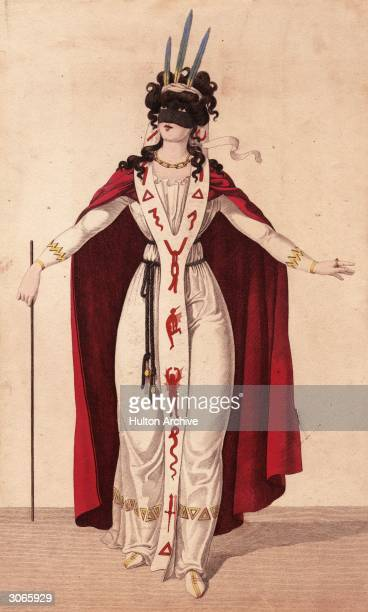 A woman with a black mask and a headdress of three large blue feathers is wearing a red cloak over a white dress with a floor length collar decorated...