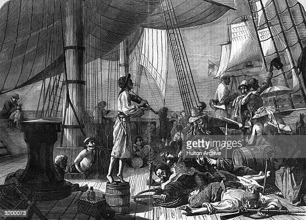A young man stands on a barrel to play a violin while pirates sprawl on deck armed to the teeth and in the background an American ship comes to the...