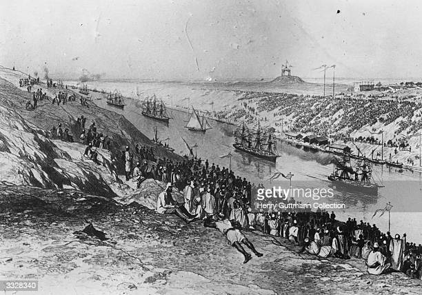 Crowds watch a procession of ships on the Suez Canal.