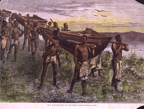 Native Africans carrying a boat in sections overland...