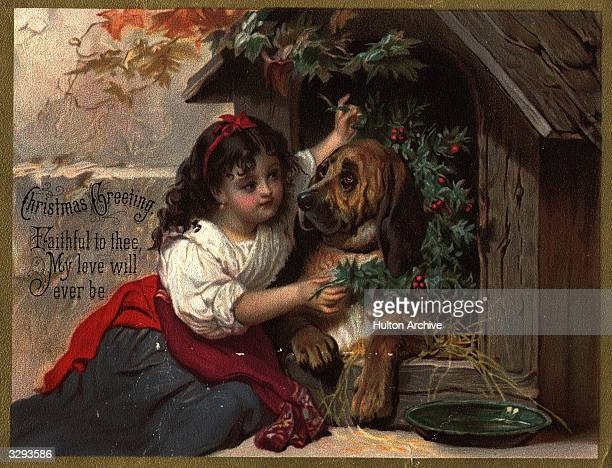 A young girl decorates a dog's kennel with holly
