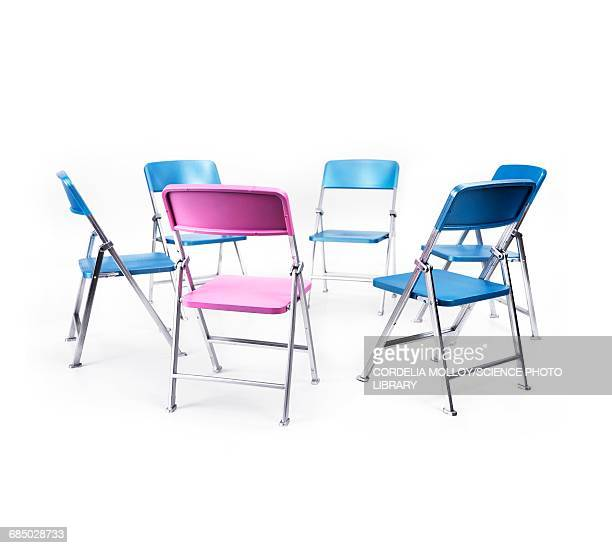 Circle of blue chairs with one pink chair