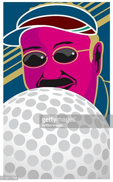Close-up of a golf ball in front of a mid adult man