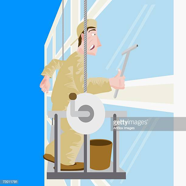 Close-up of a mid adult man cleaning the windows of a building