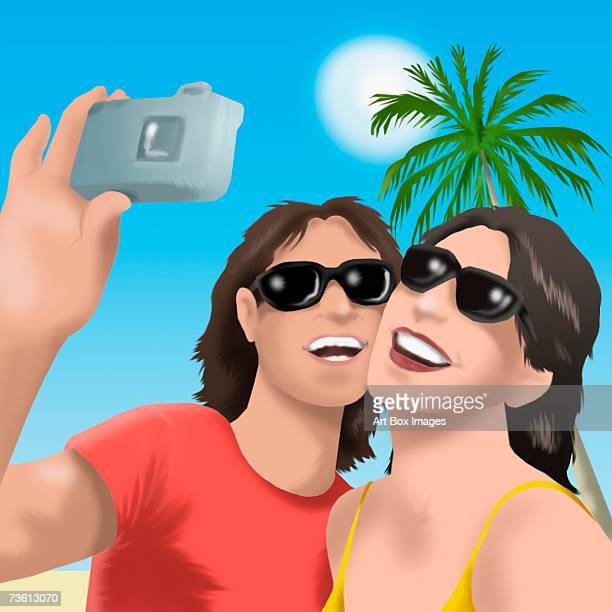 Close-up of a young man with a young woman taking a photograph with a digital camera