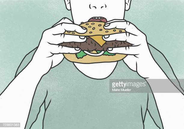 Close-up of man eating hamburger against colored background