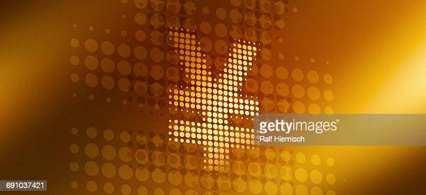 Close-up of spotted yen sign over gold colored background