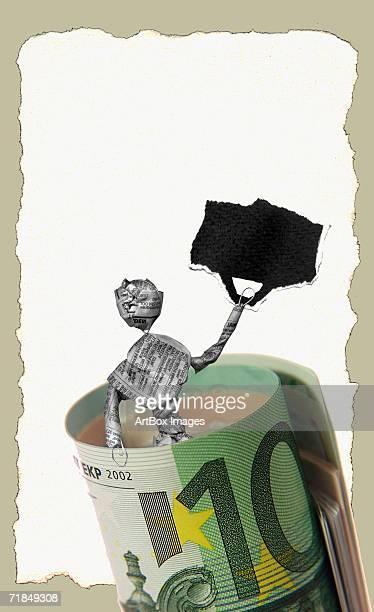 ilustraciones, imágenes clip art, dibujos animados e iconos de stock de close-up of the newspaper figurine of a man in a roll of money - fajo de billetes