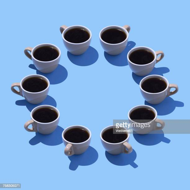 Coffee cups building circle on light blue ground, 3D Rendering