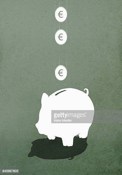 Coins falling in piggy bank against green background