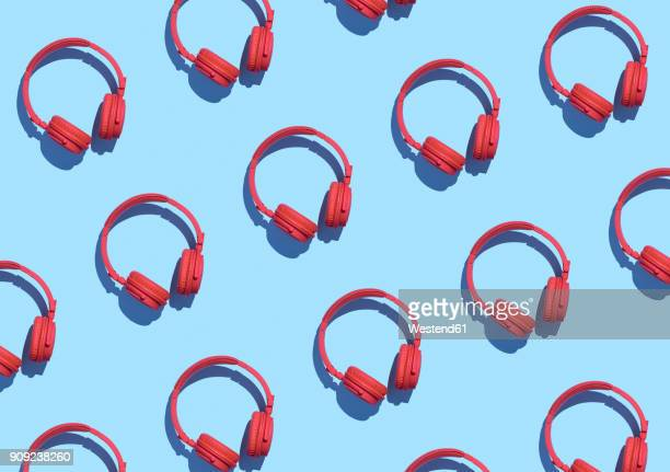Collection of red wireless headphones on light blue background, 3D Rendering