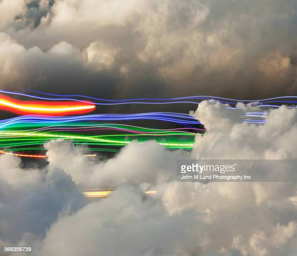 colorful light trails over puffy clouds in sky - digital enhancement stock illustrations