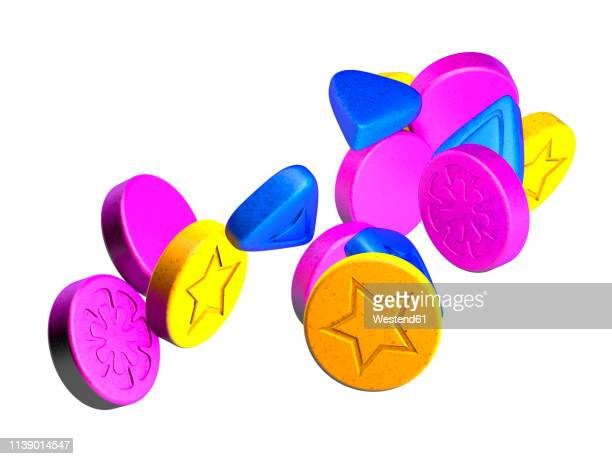 colourful ecstasy pills on white ground, 3d rendering - consumerism stock illustrations