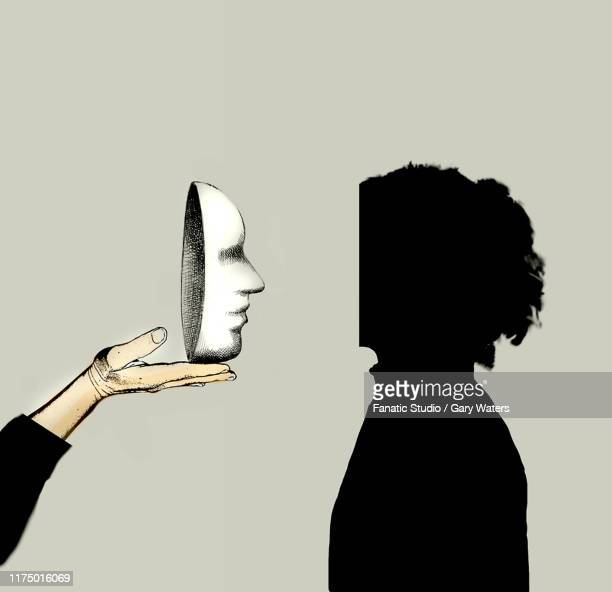 concept image of a hand presenting a mask to a faceless woman depicting identity and psychological disorder - philosophy stock illustrations