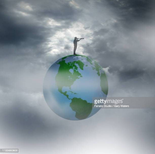 concept image of a man standing on a world looking through a telescope against a dark sky depicting a dark future.