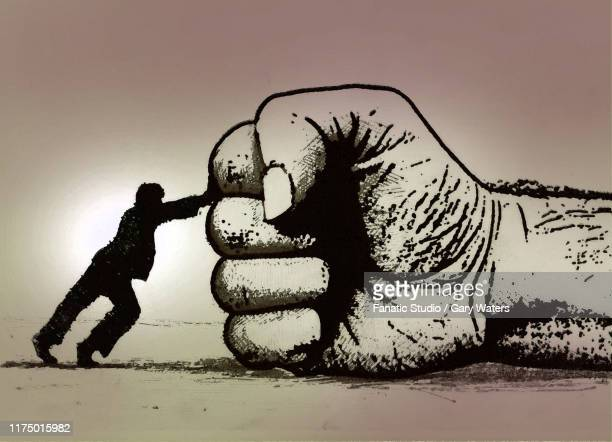 concept image of a small man pushing against a large fist depicting resistance - unfairness stock illustrations