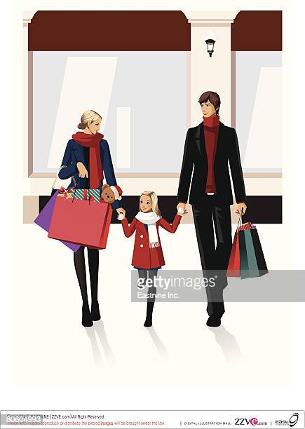 Couple carrying shopping bags and walking with their daughter
