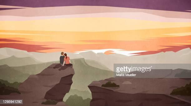 couple enjoying majestic scenic mountain landscape at sunset - sunset stock illustrations
