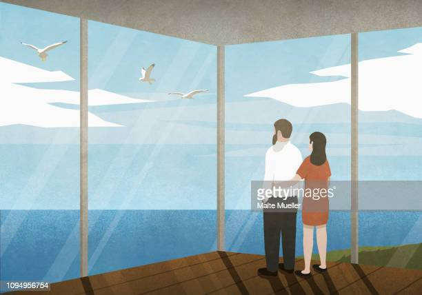 Couple enjoying ocean view from beach house