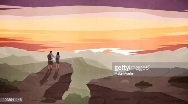 illustrazioni stock, clip art, cartoni animati e icone di tendenza di couple hiking and enjoying scenic majestic mountain view at sunset - guardare il paesaggio