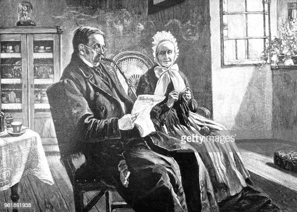 Couple in living room reading newspaper