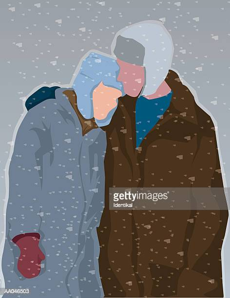Couple in winter clothing walking in snow