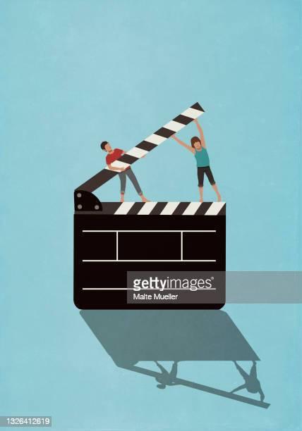couple lifting film slate - full length stock illustrations