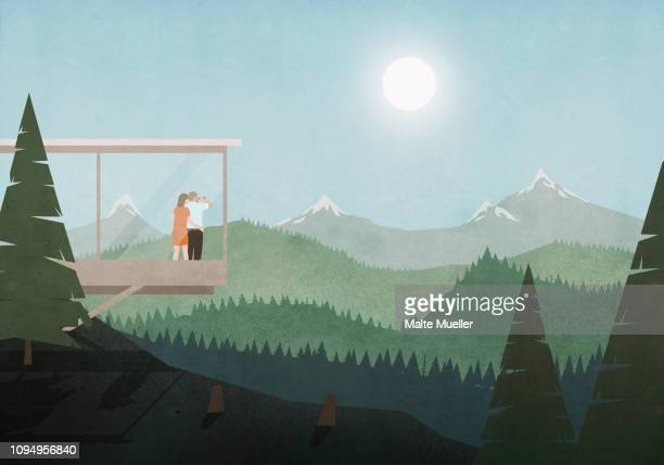 couple looking at idyllic, sunny mountain and forest view from glass house - beauty stock illustrations