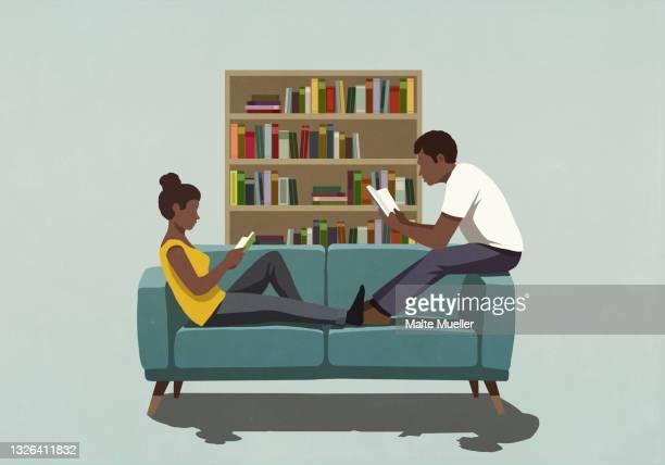 couple reading books on living room sofa - leisure activity stock illustrations