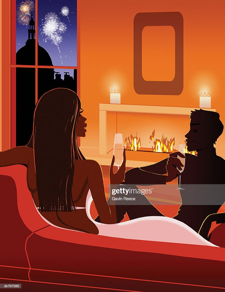Couple Relaxing By The Fireplace And Drinking Champagne