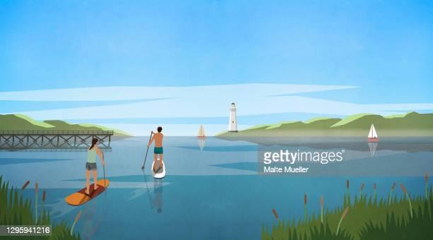 couple stand up paddleboarding on idyllic summer lake - leisure activity stock illustrations