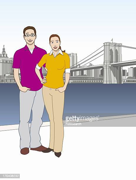 Couple standing in front of East River with the Brooklyn Bridge in the background