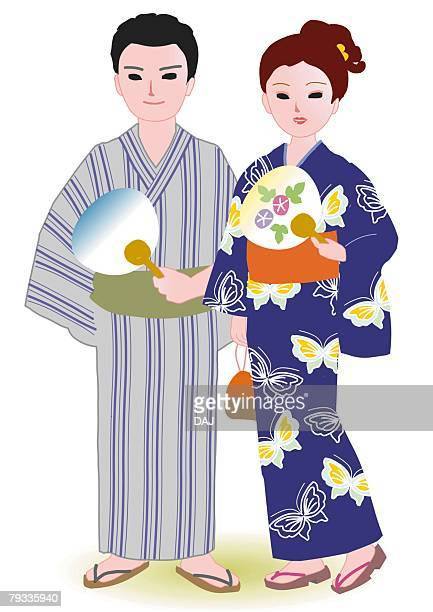 Couple standing side by side and holding paper fans in Japanese style clothing, front view, Japan