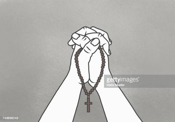 cropped image of clasped hands holding rosary beads against gray background - christianity stock illustrations