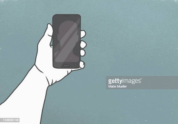 Cropped image of hand holding smart phone against gray background
