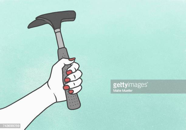 Cropped image of woman holding hammer against blue background