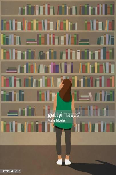 curious woman standing at towering bookshelf - exploration stock illustrations