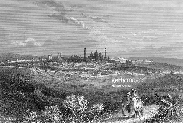 Delhi with an encircling wall seen from the surrounding countryside. In the foreground an elephant with howdah and passengers. Original Artwork:...