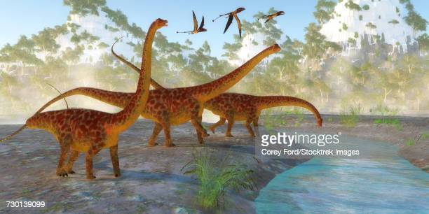 Diplodocus dinosaurs drink from a river as a flock of Dimorphodon fly above.