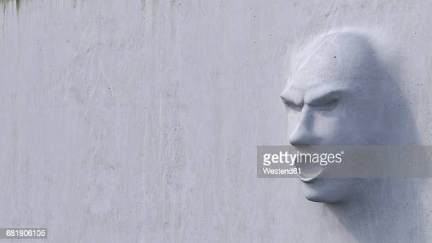 Displeased face growing out of concrete wall