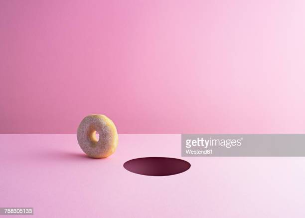 doughnut and hole on pink ground - copy space stock illustrations