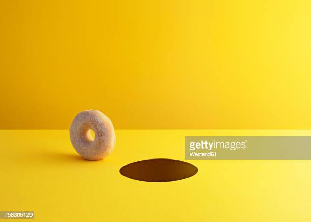 doughnut and hole on yellow ground - copy space stock illustrations