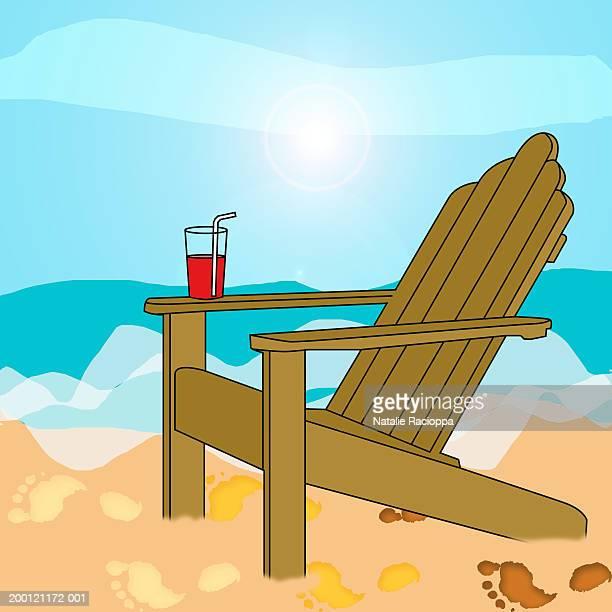 Drink balanced on arm of deckchair on beach