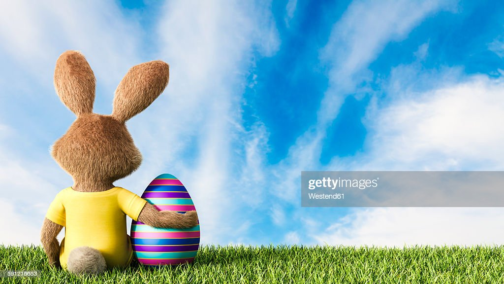Easter bunny sitting on grass with arm around Easter egg : Stock Illustration